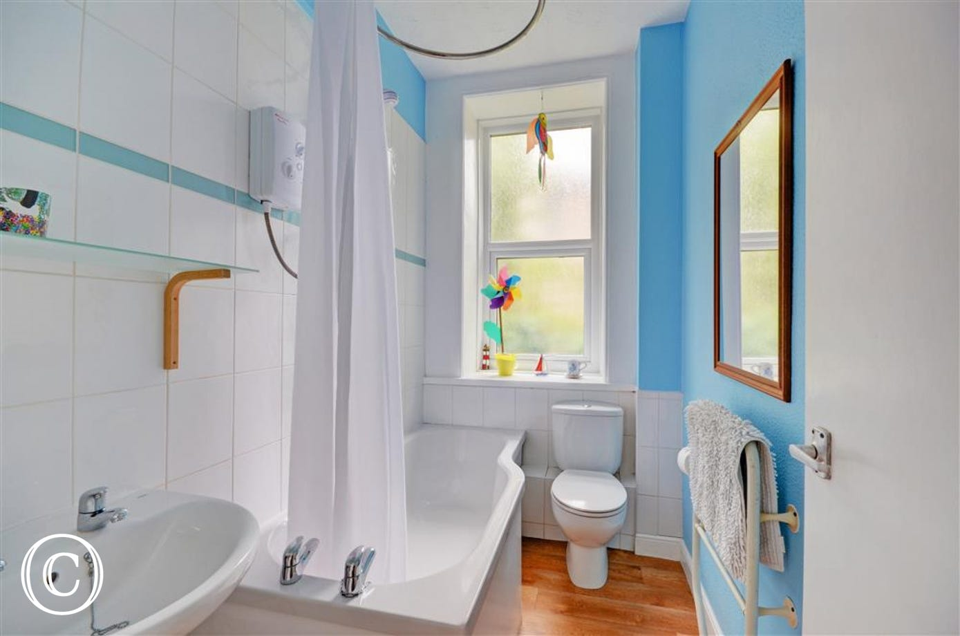 Bathroom with shower over the bath, wc and basin